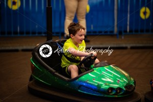 Happy young boy rides electric bumper car amusement ride on shore boardwalk - Kelleher Photography Store