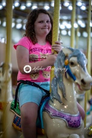 Happy young girl having fun on boardwalk amusement ride - Kelleher Photography Store