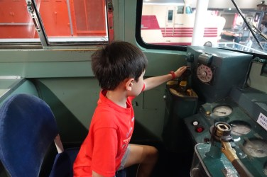 Child sitting at train controls