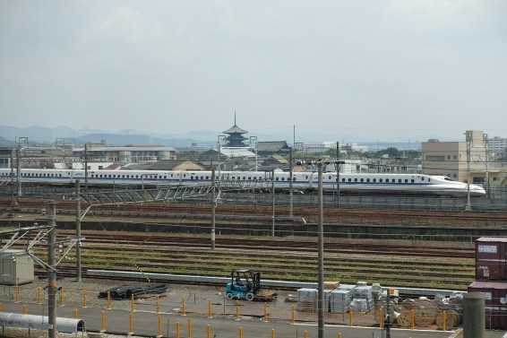 Shinkansen racing past a pagoda