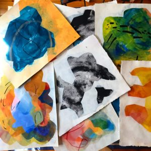 A close up of several small Rachel Hawkes Cameron paintings, piled in random layers
