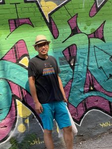 Eddy Xuan, Co-Founder of AXS Biomedical Animation Studio, standing in a black t shirt with a hat and glasses in front of graffiti alley wall in toronto