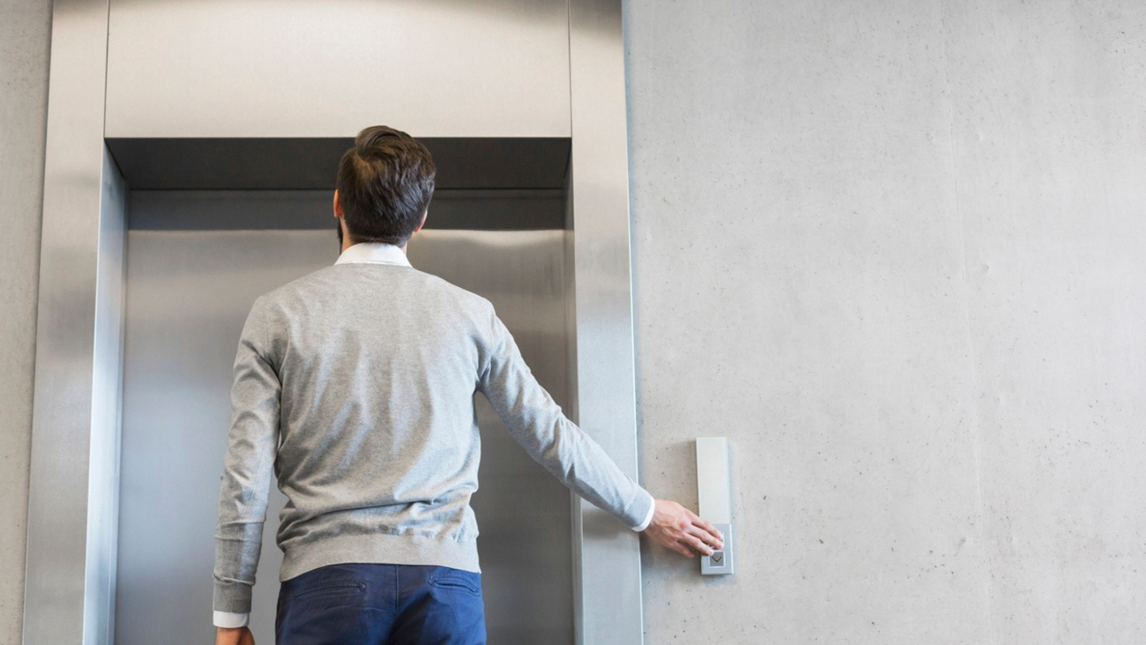 young well dressed man pressing elevator button and looking at elevator doors