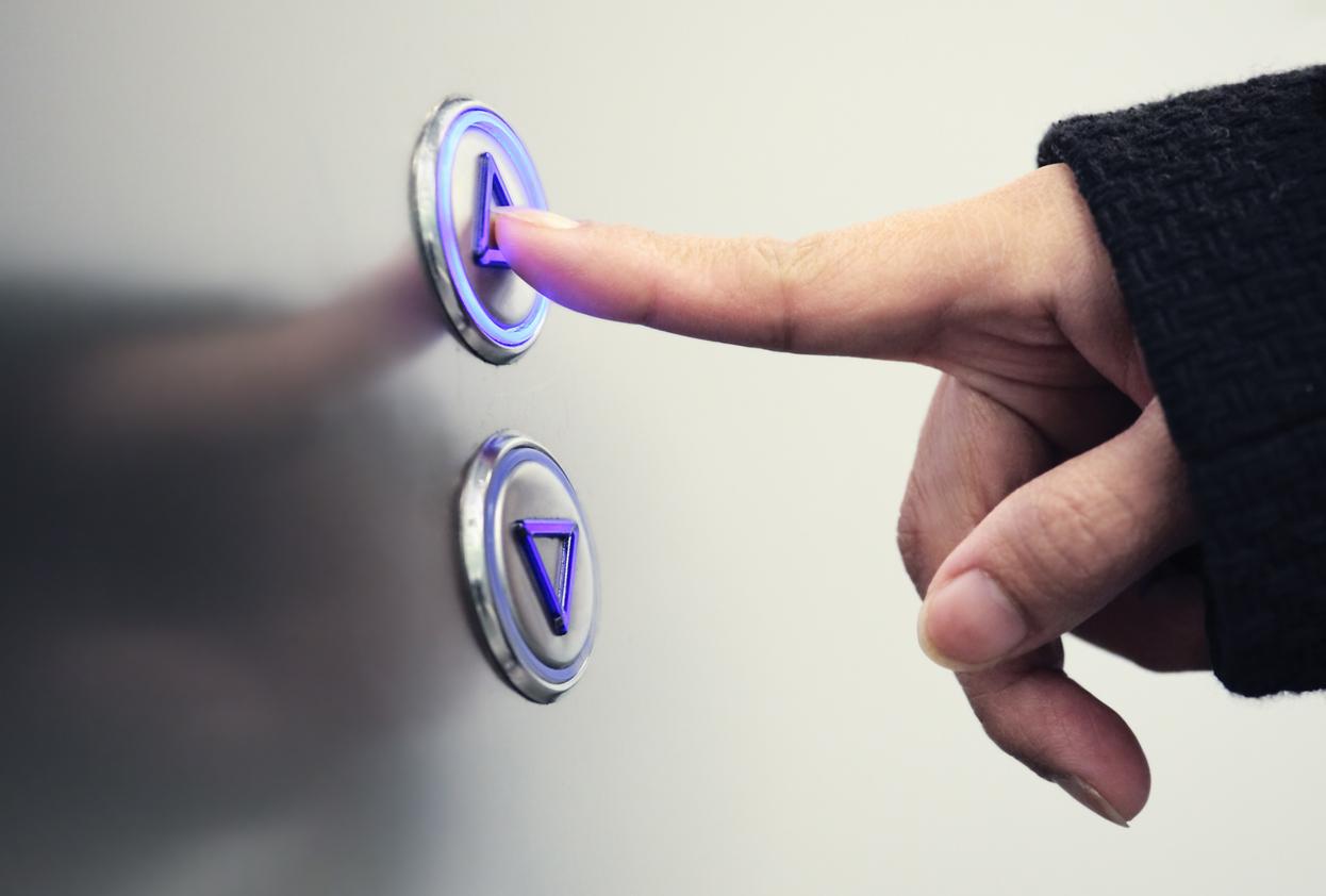 Hand pushing elevator button upward, black shirt visible