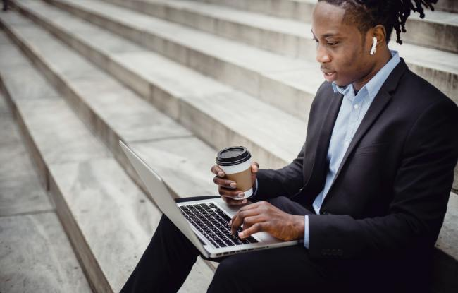 Young man with blazer sitting on steps with coffee and laptop