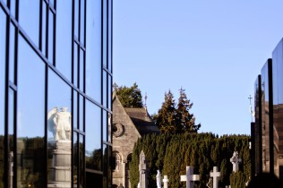 Modern museum building at Glasnevin catches the reflection of the old monuments.