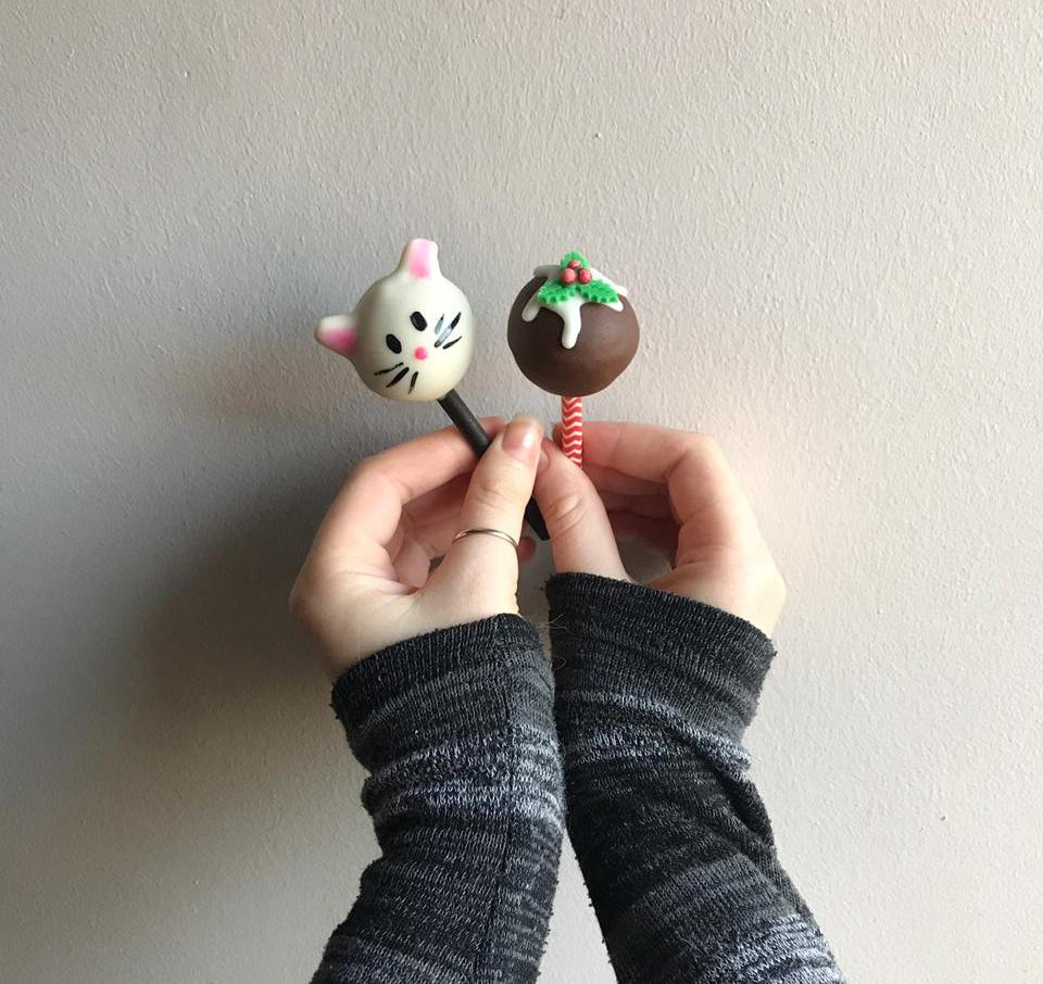Storm holding cake pops against white wall. One pop is shaped like a cat, the other is a christmas themed bauble.