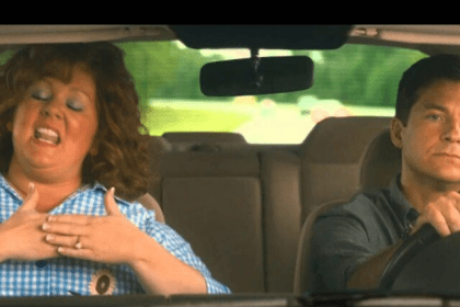 Melissa McCarthy singing to every song on the radio, with an unamussed passanger.