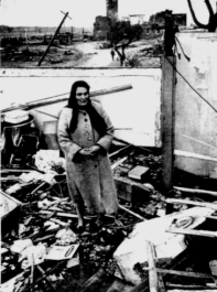 A woman stands amid the ruins of her home in Watertown, WI.