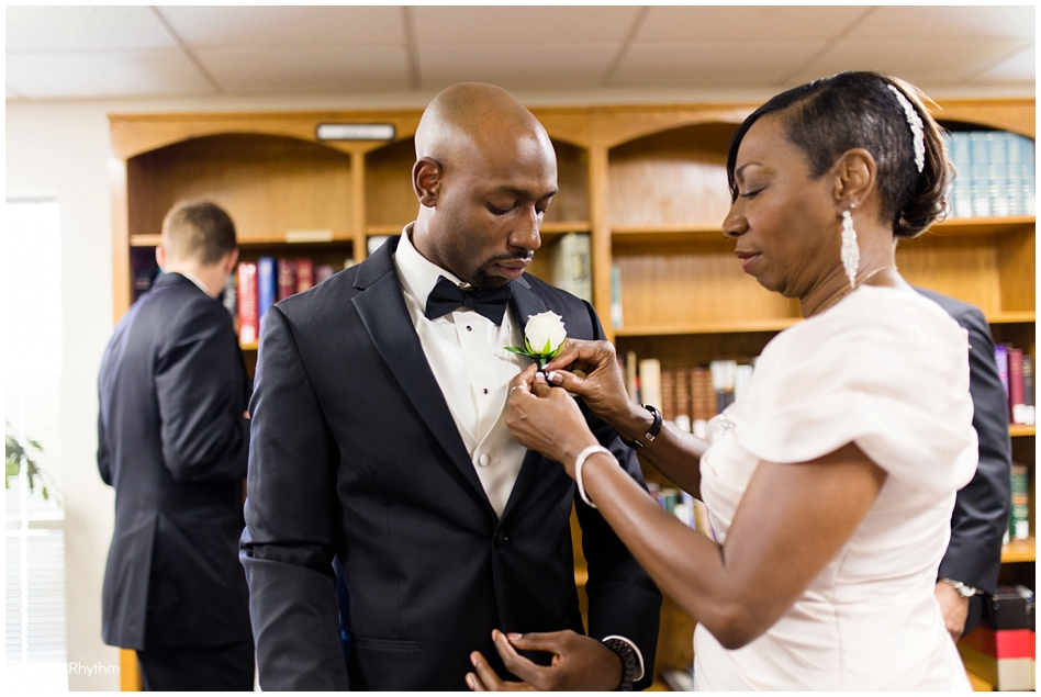 The groom's mother pinning the boutonniere on her son.