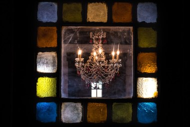 Photograph of the Storybook Barn Bride's Room Chandelier framed by the colored stained glass of the door