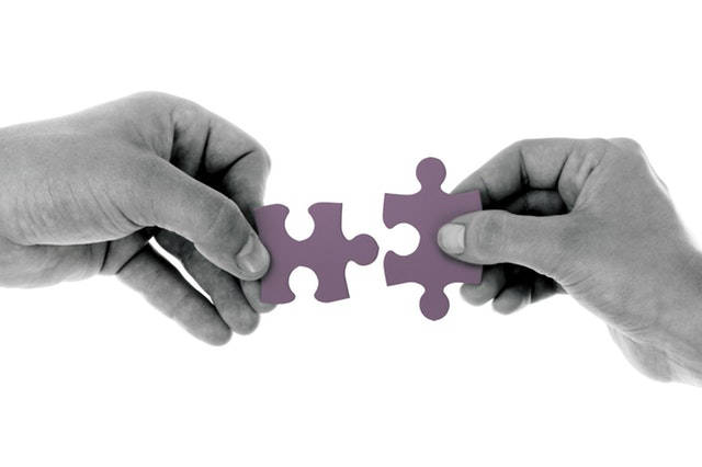 Two puzzle pieces being fit together.