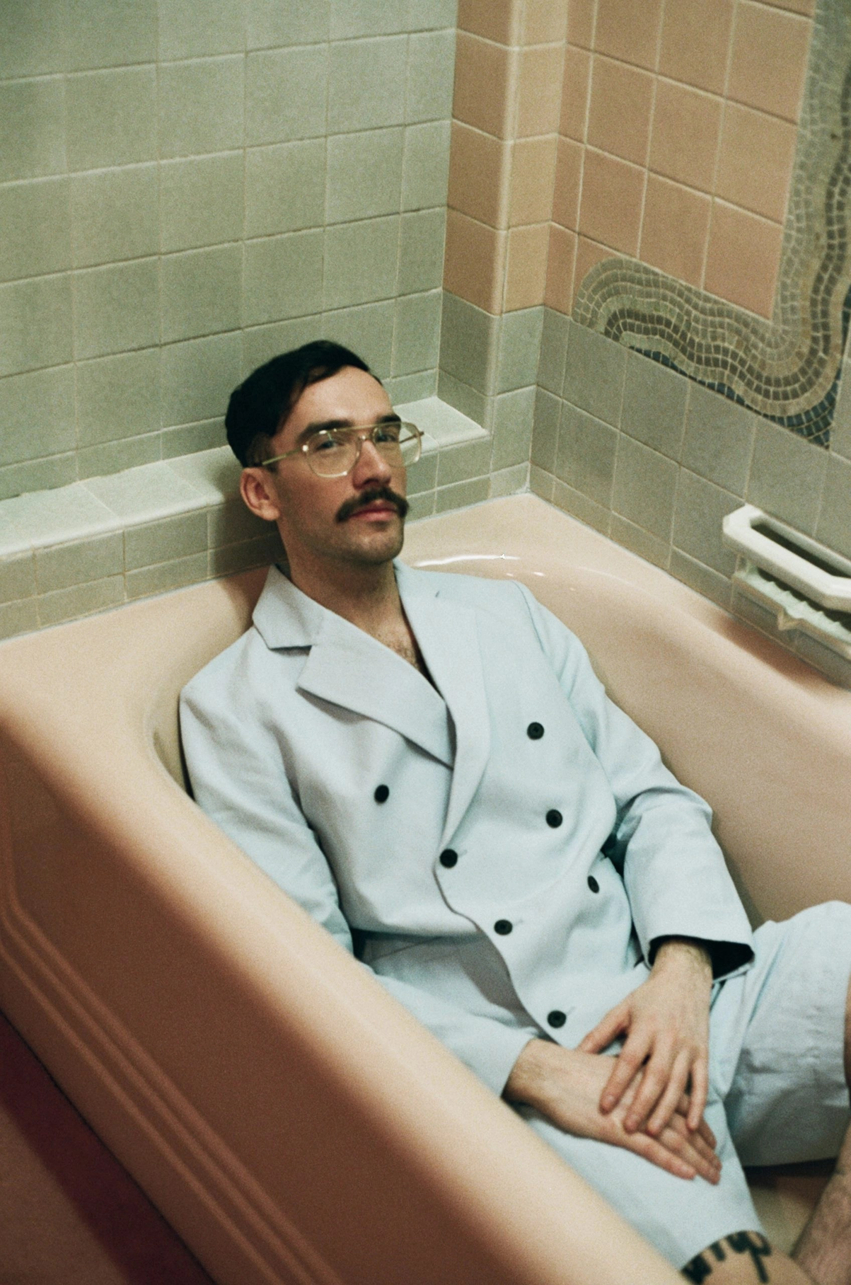 A beautifully coiffed, moustachioed man lounges in a pink enamel bathtub. Wearing a double-breasted powder-blue shorts suit, his hands are folded gently in his lap.