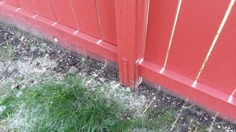 Red stained fence post with Post Buddy stakes installed