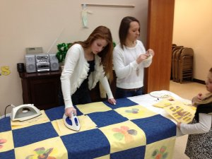 Two girls ironing colored flowers onto fabric squares