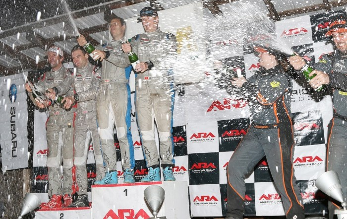 The top three overall at the podium's champagne spray at the Tioga County Fairgrounds at the conclusion of the 2017 Waste Management Susquehannock Trail Performance Rally (Lori Lass Photography)