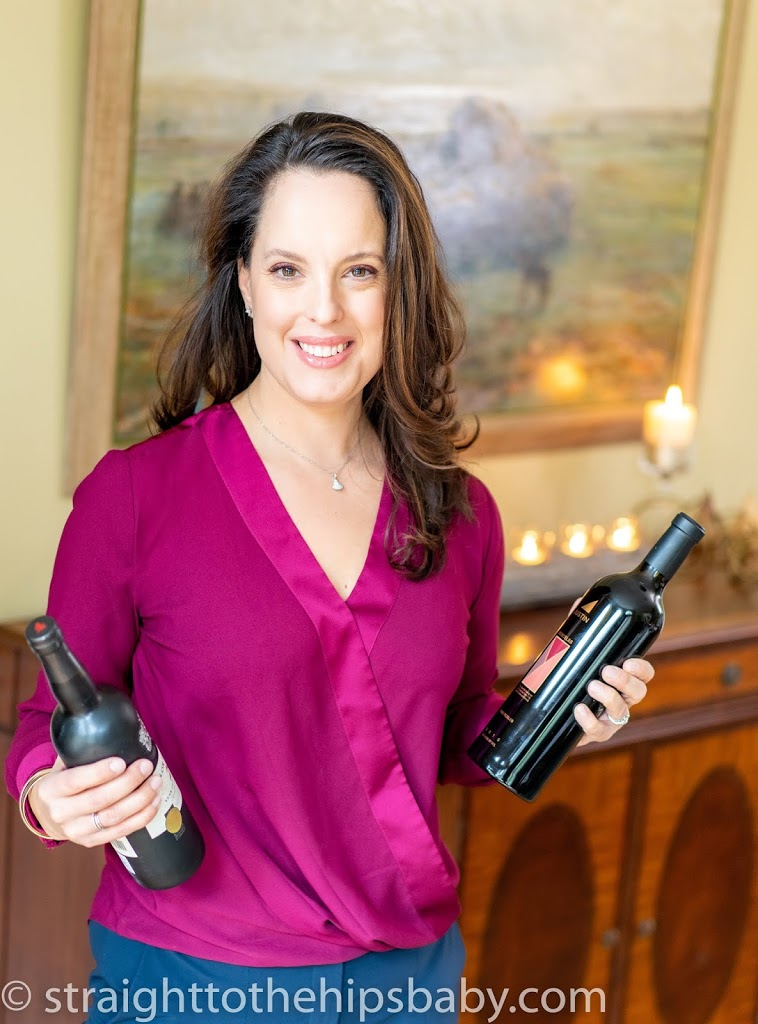 Woman with dark hair and a cranberry colored blouse, smiling and holding a bottle of wine in each hand