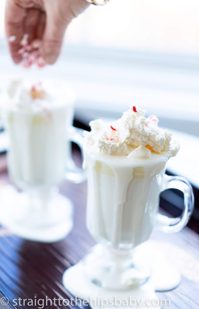 two overflowing glass mugs of peppermint white hot chocolate with whipped cream and peppermint pieces being sprinkled on top