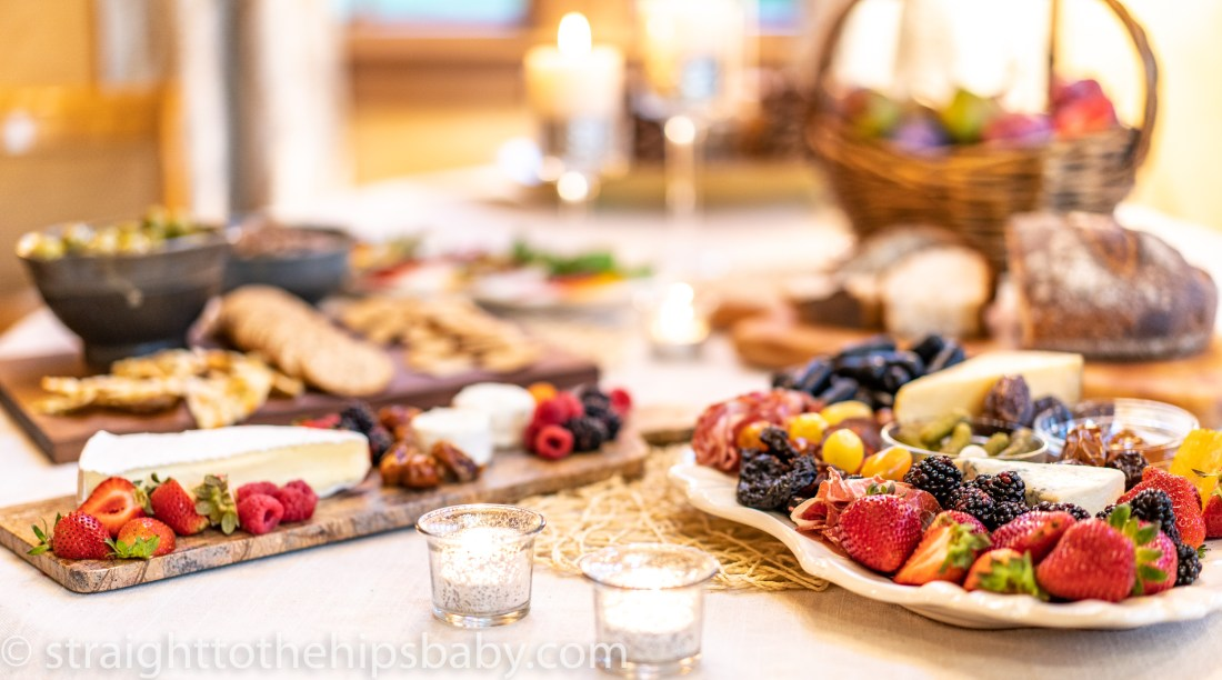 Two laden charcuterie platters on a large table with candles