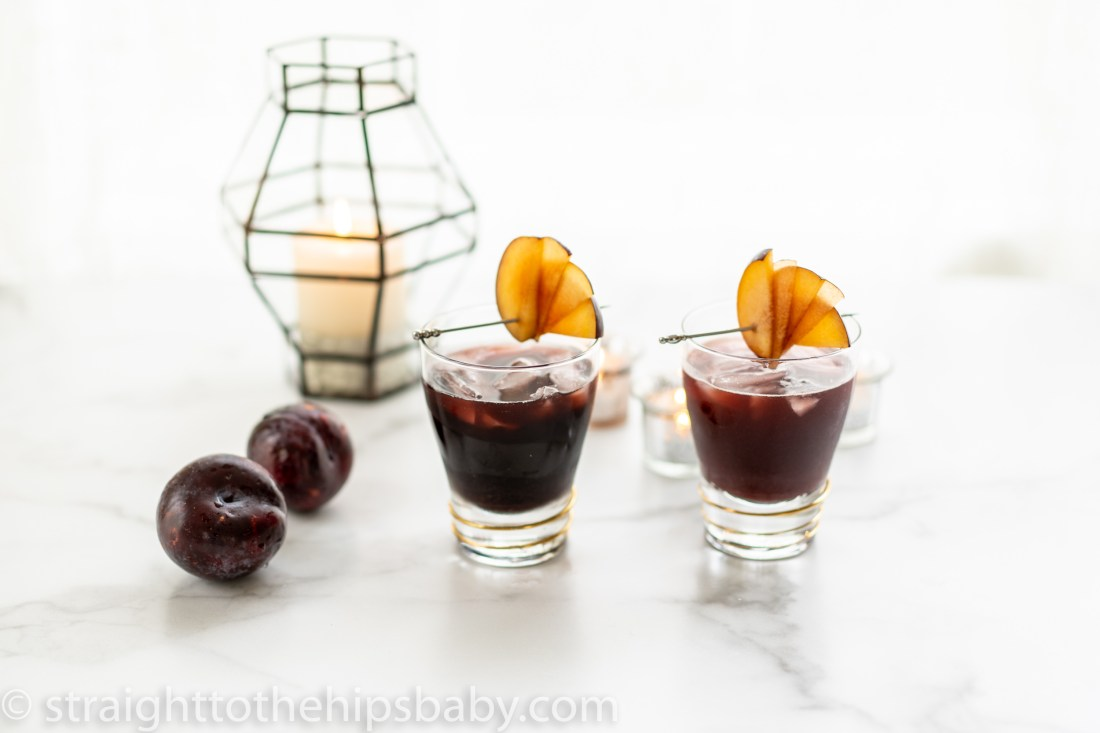 two plum colored cocktails against a light colored background