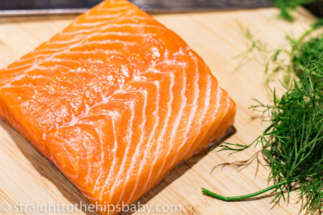 a salmon filet with dill, sitting on a wooden cutting. board