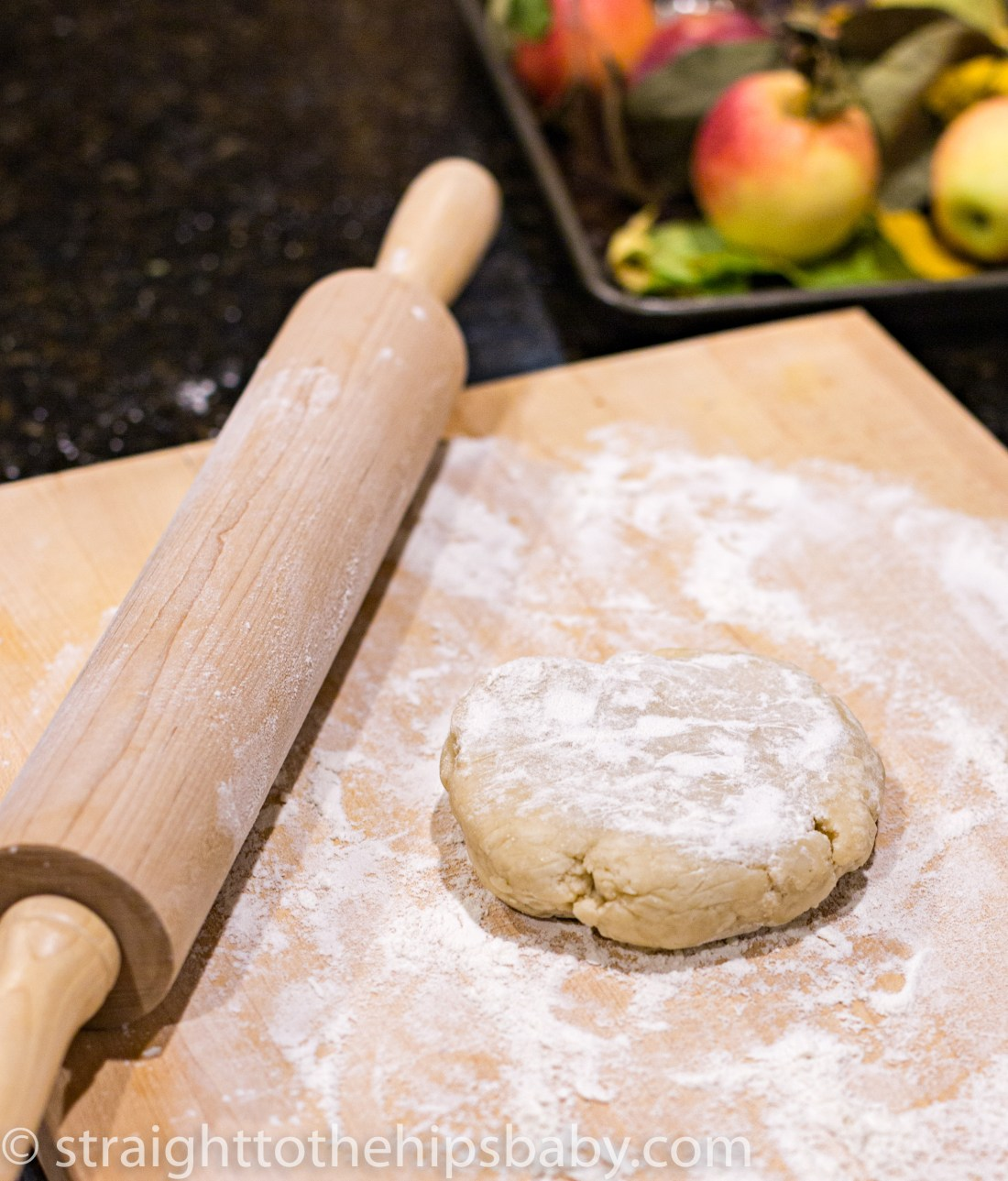 a disk of dough sitting on a floured cutting board, with a wooden rolling pin beside it