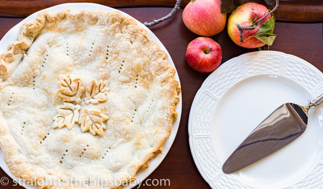 a finished golden brown old fashioned apple pie in a white ceramic pie plate, on a mahogany table, with a white plate and pie cutter beside it