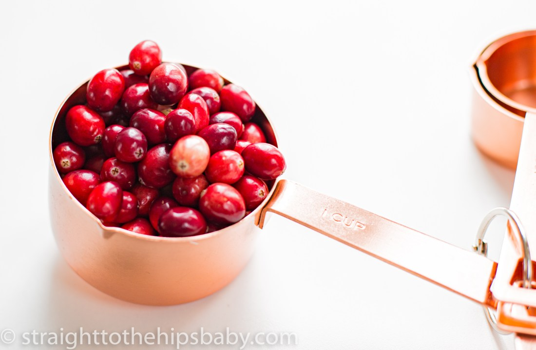 whole bright red cranberries in a shiny copper measuring cup