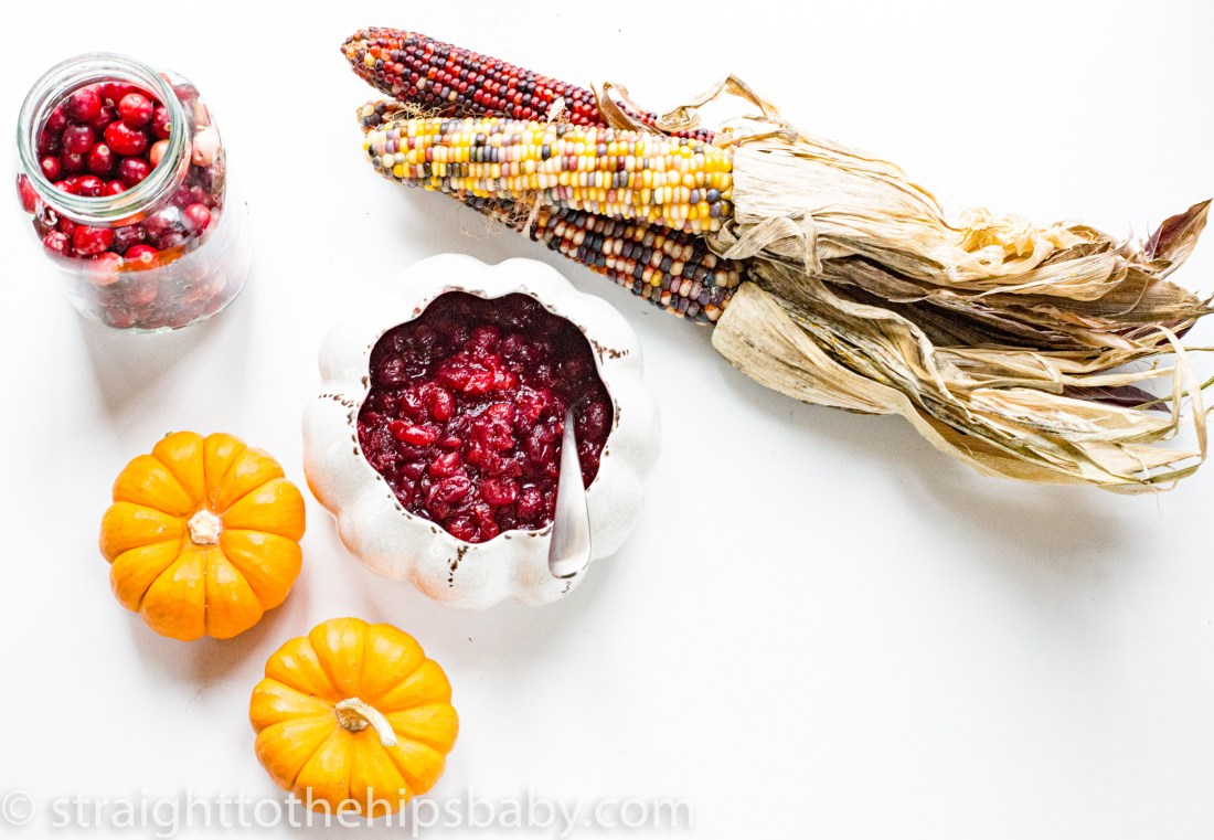 Ruby red cranberry sauce in a white bowl, with orange pumpkins on a white background