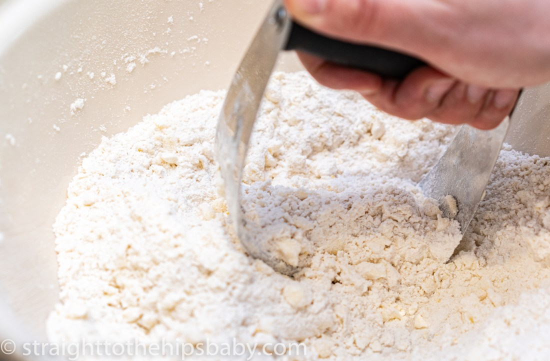 using a pastry cutter to cut the butter into the flour mixture