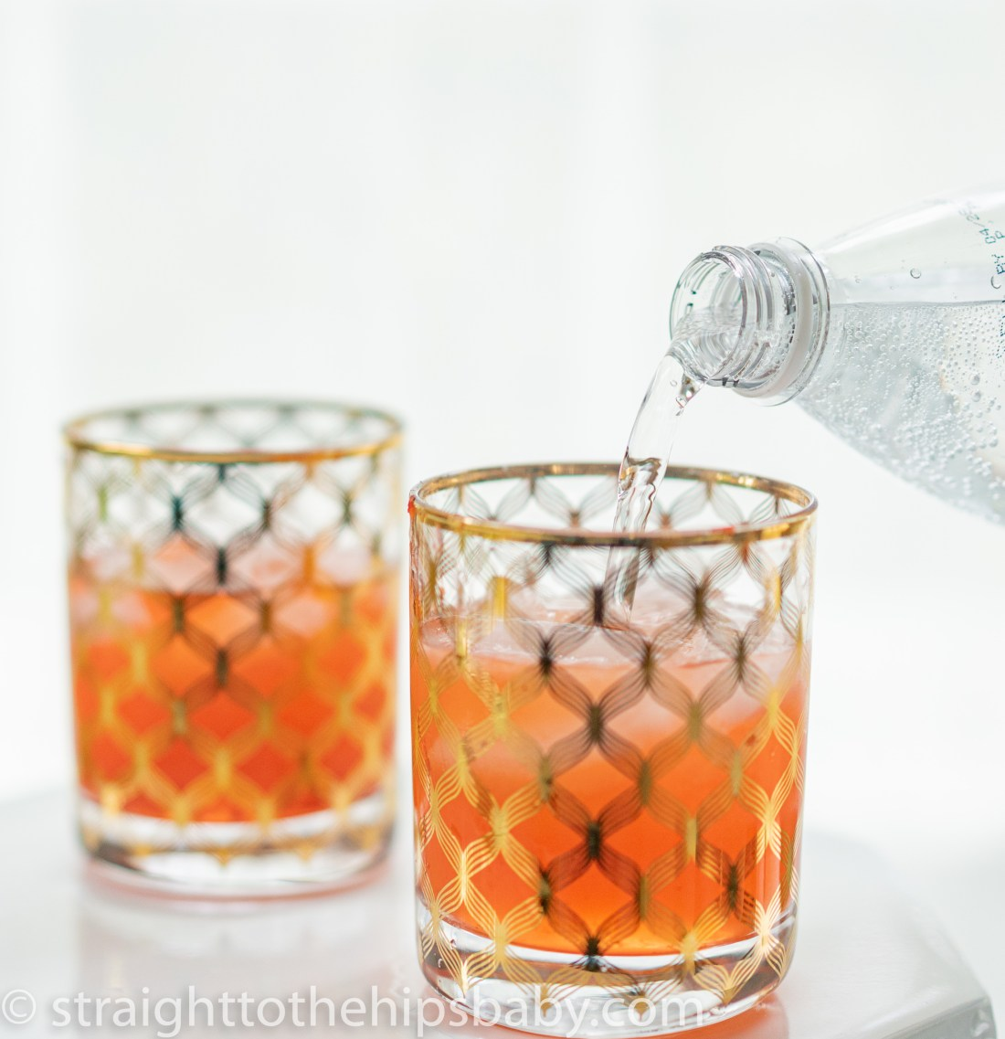 adding fizzy soda water to two finished drinks