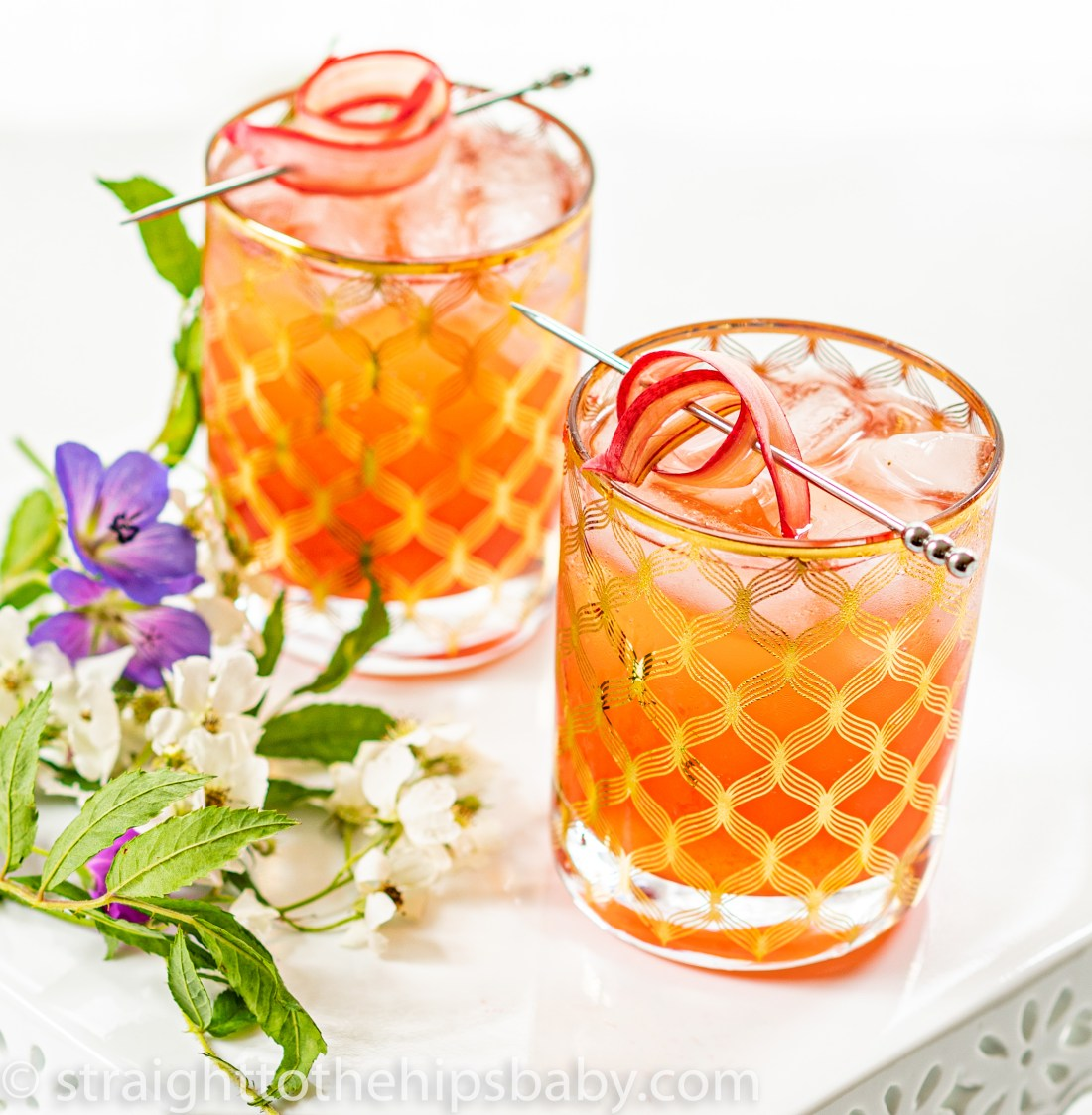 two refreshing looking pink cocktails in gold accented glasses, with floral garnishes