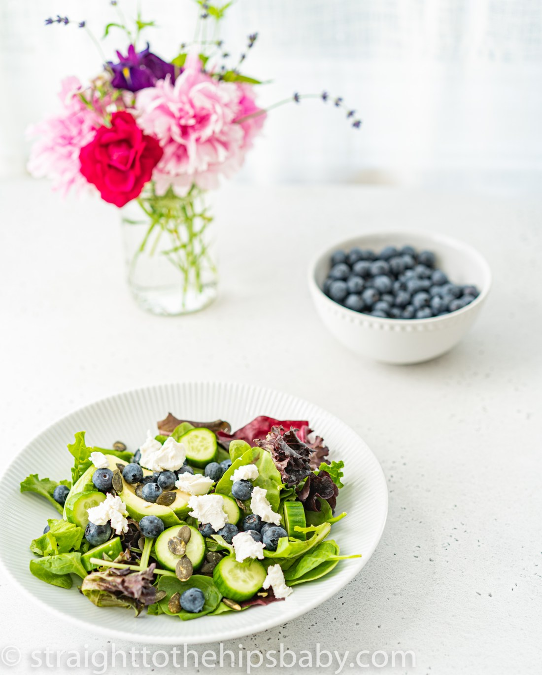 an undressed plate of blueberry goat cheese salad with a bouquet of pink flowers and bowl of blueberries blurred in the background