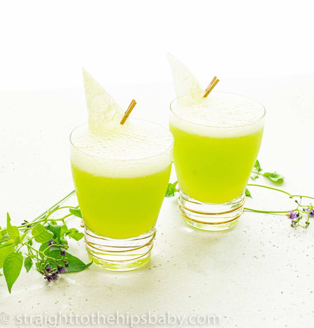 two finished frozen melonbmalls in highball glasses, garnishes with green melon