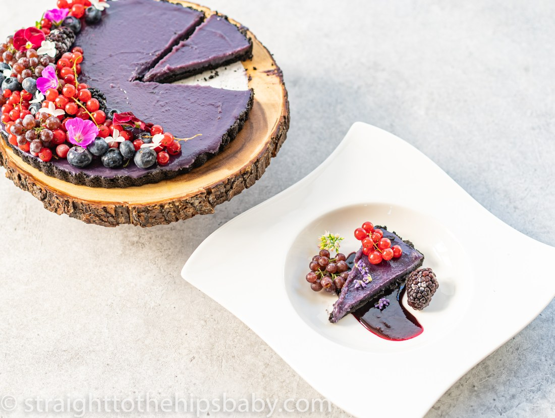 blueberry curd tart garnished with berries and flowers