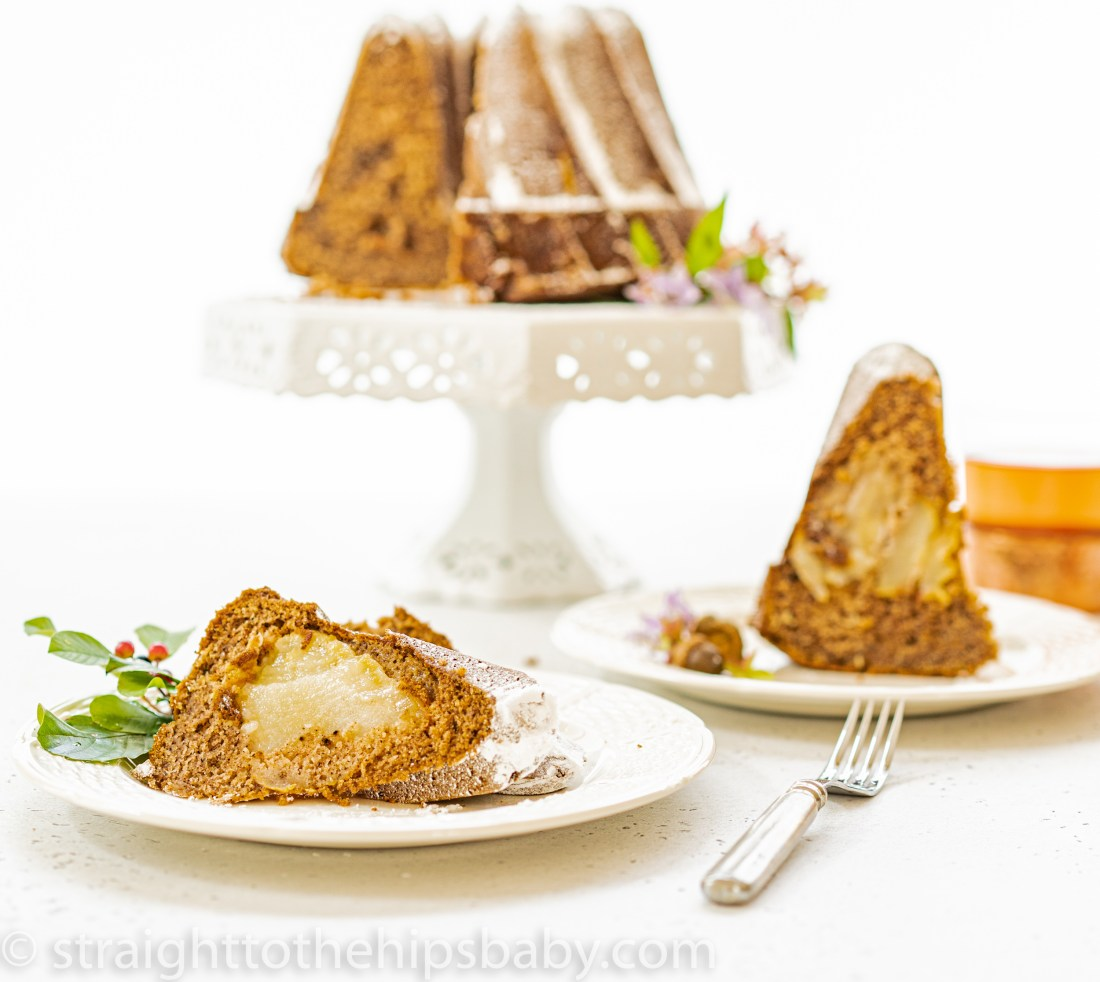 a pear Bundt Cake, two slices in the foreground, and the whole cake on a stand in the background