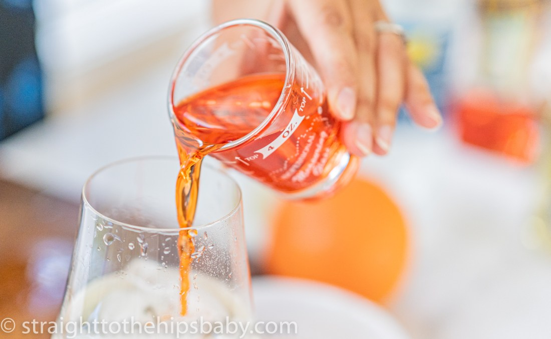 bright orange Aperol liqueur being added to a wine glass with ice and champagne