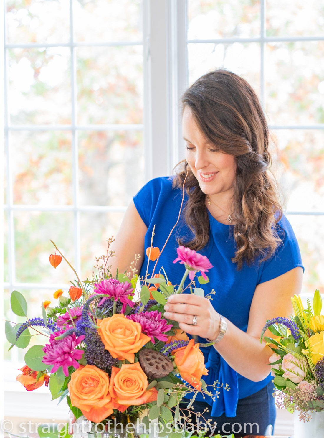 woman in a blue blouse, placing flowers in a vase.