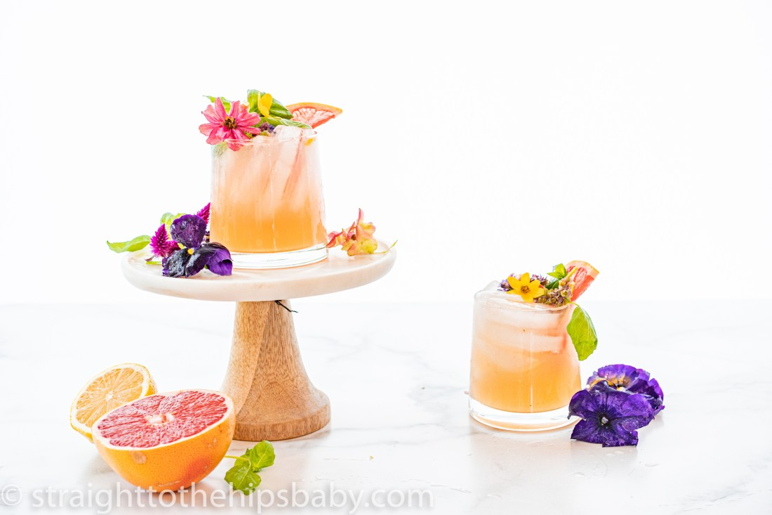 Two finished cocktails, surrounded by fresh flowers and fruit. One drink on a small cake stand and the other on a the marble background