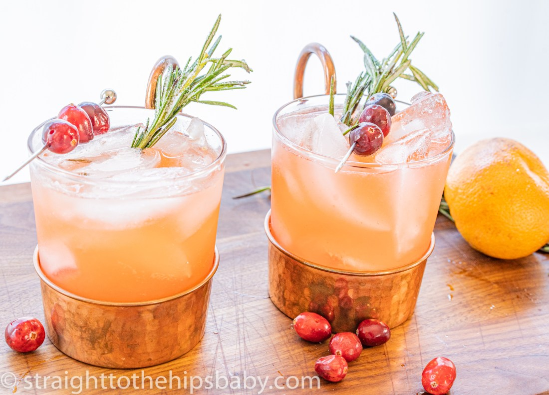 two festively decorated glasses of spiced cranberry punch with rosemary garnish