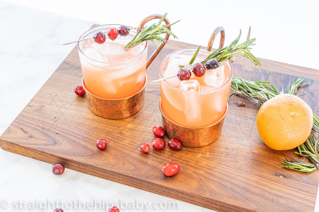 two glasses of punch on a wooden cutting board with scattered herbs