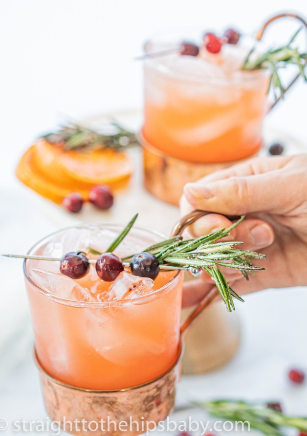 a woman's hand holding a cup of spiced cranberry punch with fresh rosemary garnish