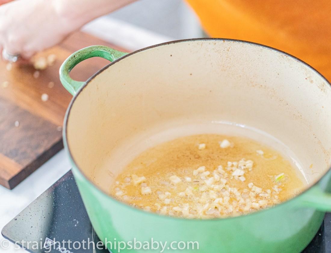 frying garlic in a green pot