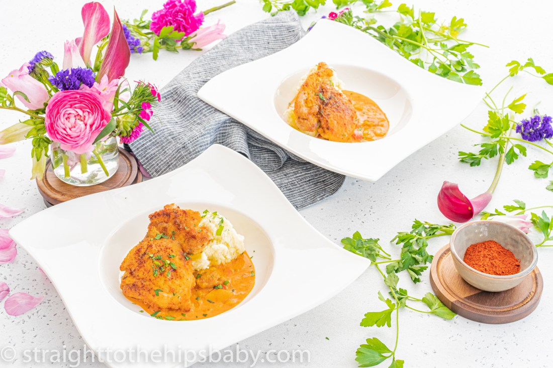 two square white bowls filled with bright orange chicken paprikash