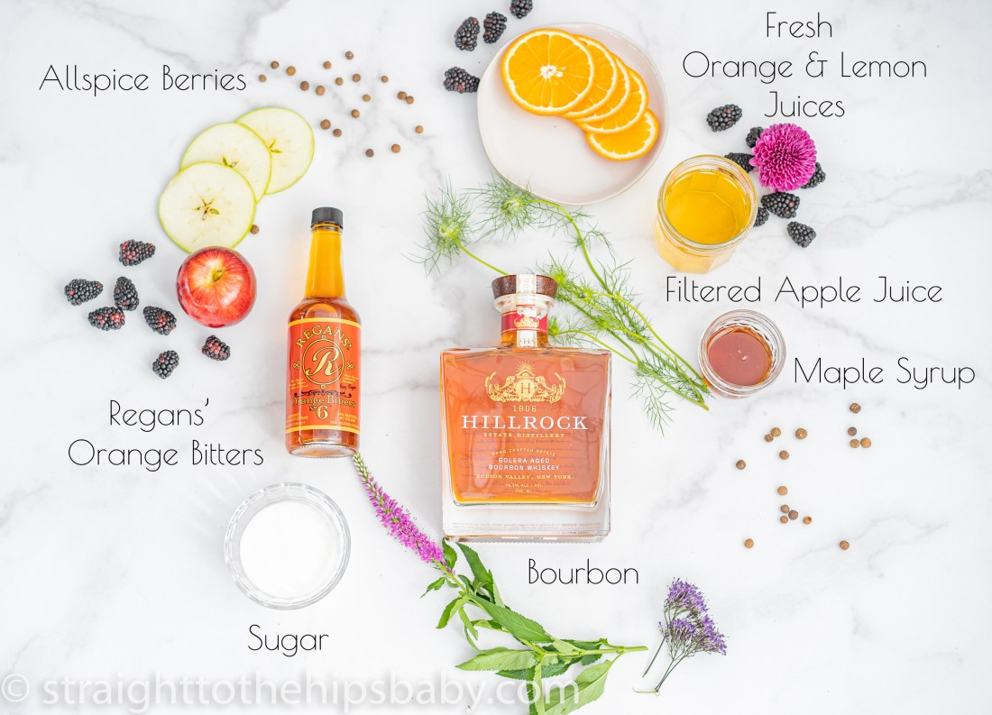 a flat lay of ingredients including bourbon, Regans' orange bitters, apples, oranges, maple syrup, for the apple & orange bourbon sour with maple allspice simple syrup