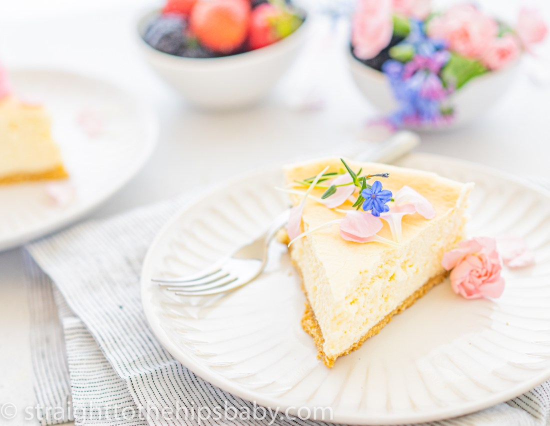 a single piece of sesame cheesecake on a white plate, garnished with spring flowers