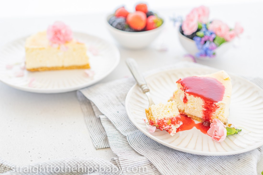 2 pieces of gluten free and sugar free cheesecake on a white background, one smothered in a plum sauce