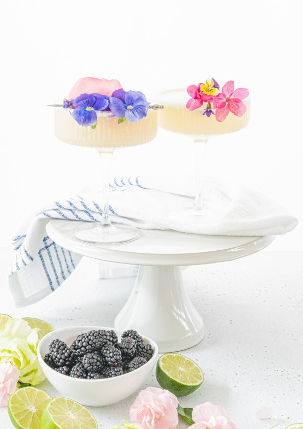 2 Creamy Coconut Pearl Palomas on a cloth and white cake stand, surrounded by fresh limes and berries