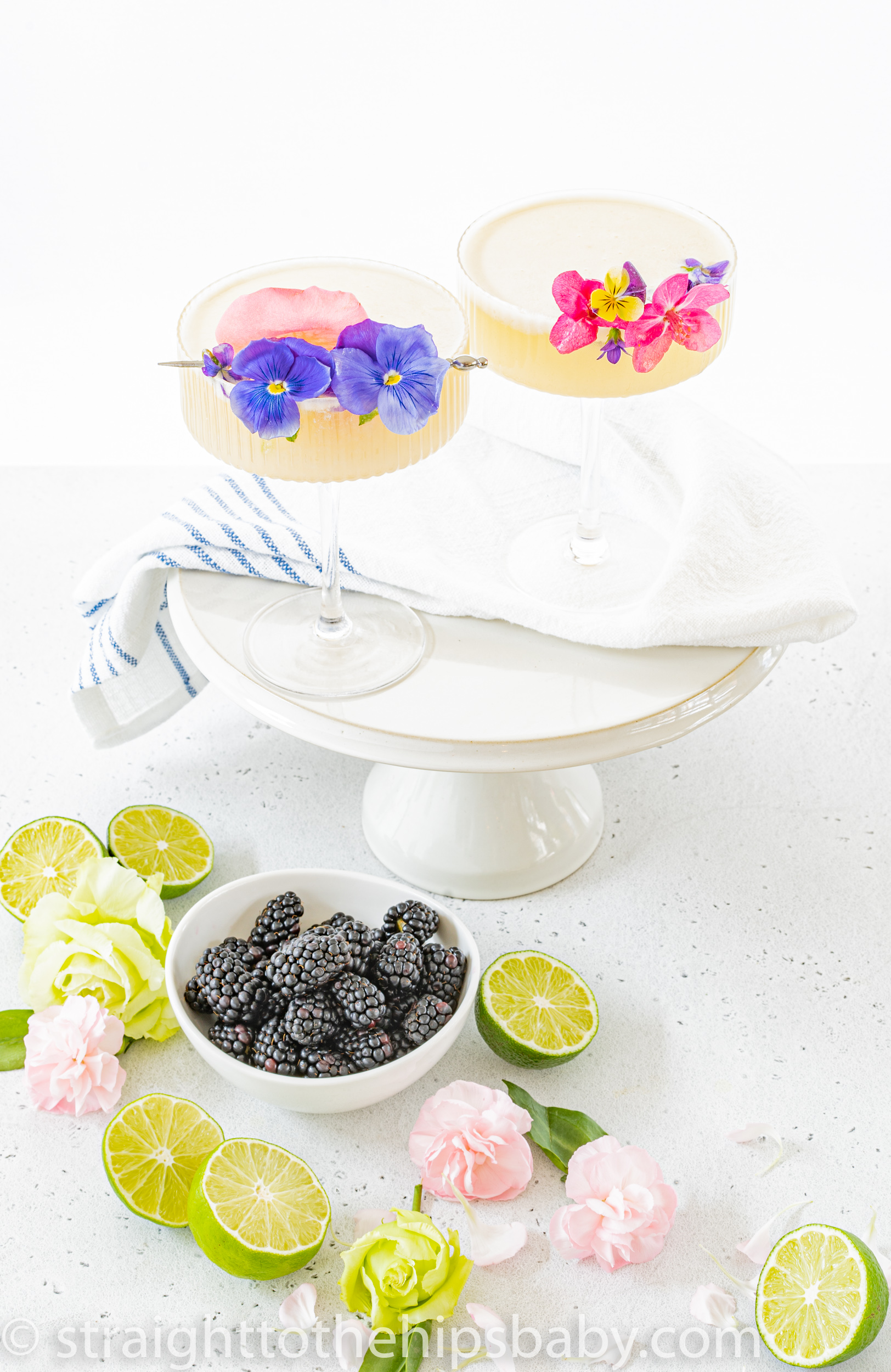2 creamy coconut pearl Palomas on a blue and white cloth and cake stand, with limes and fresh berries