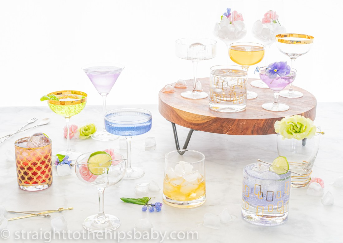a collection of clear glassware filled with pastel colored drinks, on a white background. Coupes, highballs, and old fashioned glasses are garnished with ice and flowers